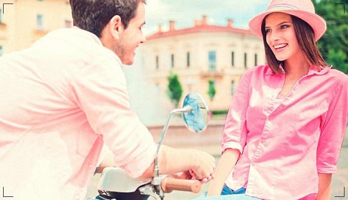 hombre conversando con una mujer en su moto