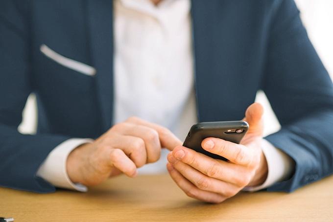 hombre revisando sus llamadas en su teléfono móvil