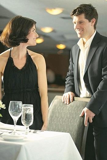 hombre siendo un caballero con una mujer en un restaurante