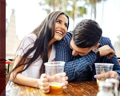 hombre y mujer riendo juntos tomando unas bebidas
