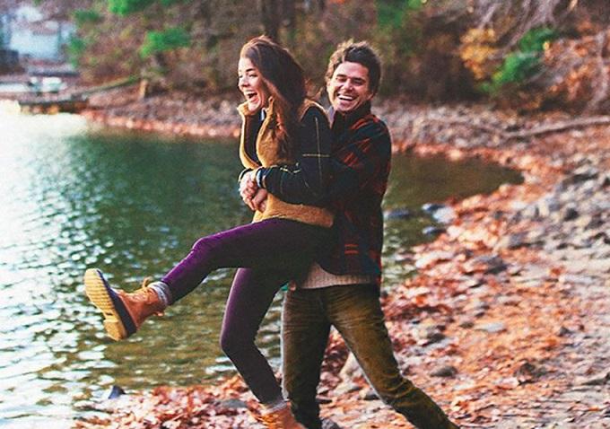 hombre y mujer sonrientes en la orilla de un lago