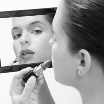 mujer maquillandose frente a una espejo