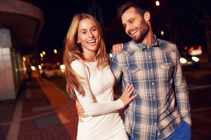mujer riendo con un hombre en la calle